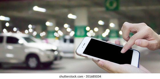 Woman using touch screen mobile phone with blur cars parking