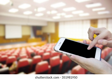 Woman using touch screen mobile phone with Blur Red Chairs with training room