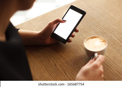Woman using a touch screen of smartphone on the wooden table, in cafe, near the window with cup of aromatic cappucino, close up