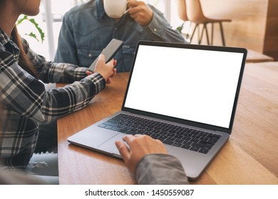 A woman using and touching on mockup laptop computer touchpad with colleagues in meeting