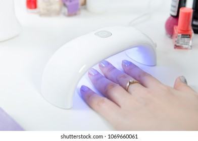 Woman using UV light dryer. Manicure, spa salon concept. Beauty and fashion.