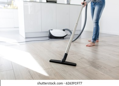 Woman using Vacuum Cleaner in Kitchen