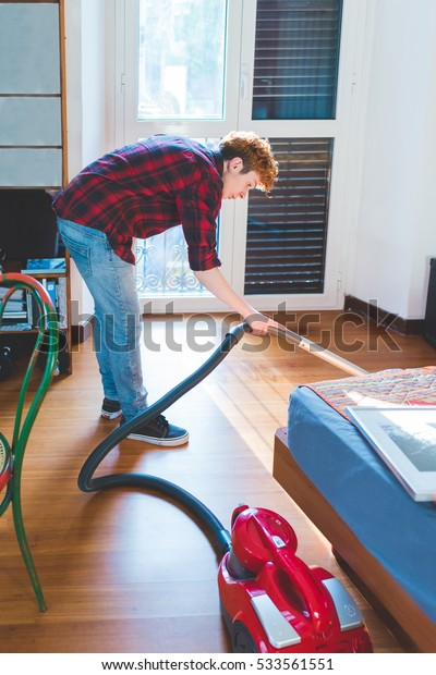Woman using vacuum cleaner on carpet at home in the living  - domestic, cleaning concept