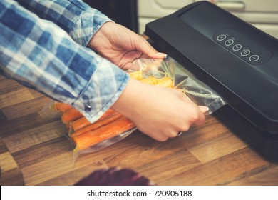 Woman using vacuum seal machine for packing carrots in plastic bags for sous vide cooking.