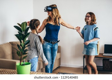 Woman using VR headset glasses virtual reality at home standing on living room with kids.