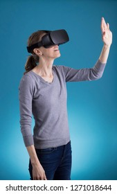 Woman using VR Virtual Reality headset on blue background.