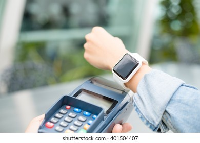 Woman using wearable watch to pay