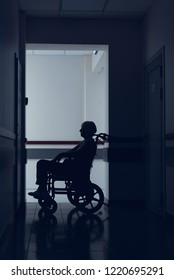 Woman is using wheelchair in clinic corridor. She is sitting in solitude in dark passageway and waiting for doctor