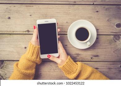 Frauen mit einem weißen Smartphone in einem warmen Pullover