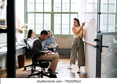 Woman using whiteboard in a small team meeting