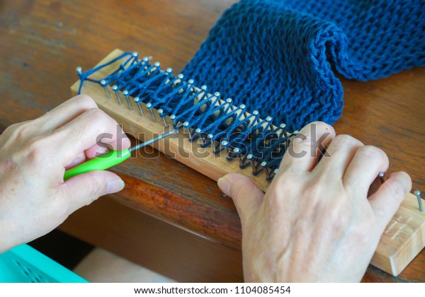 A woman using wooden loom for knitting scarf.