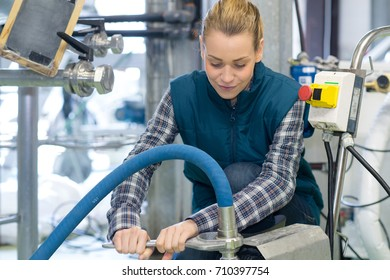 woman using wrench to tighten large nut around pipeline