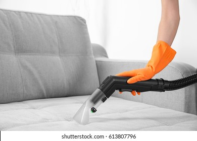 Woman with vacuum cleaner cleaning couch