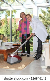 Woman vacuuming for elderly lady