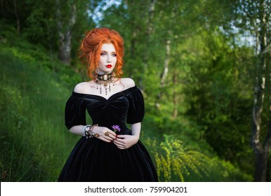 A woman is a vampire with pale skin and red hair in a black dress and a necklace on her neck against the background of nature. Girl witch with vampire claws and red lips