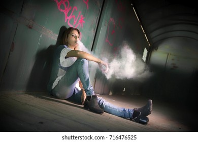 Woman vaping in an old and abandoned train wagon