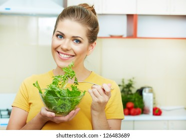 Woman with vegetarian food  standing against  home kitchen interior eating healthy food. Yellow color clothes.