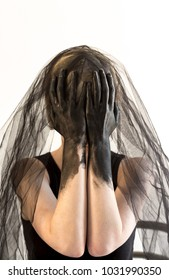 Woman with veil and hands covering her face