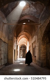 Woman in veil walking through old bazaar of Yazd lit by ray of light coming from skylight openings.