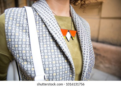 A woman in a velvet olive jacket and a gray waistcoat with a glass necklace. Triangular glass necklace on the girl's chest. Stylish necklace