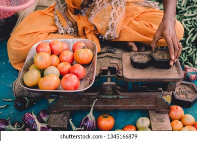 Woman vendor selling fresh tomatoes in a farmer's marketplace. Tomatoes weighed using traditional weighing balance.