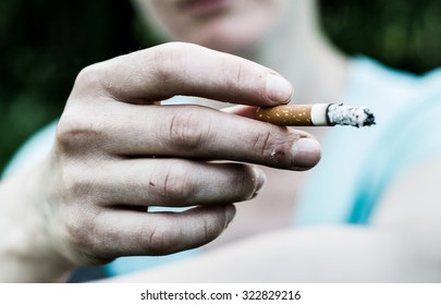 Woman in a very bad mood, holding in his hand, holding a smoldering between his fingers (fuming) cigarette. Cigarette close-up.