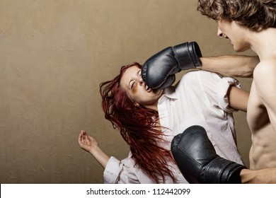 Woman victim of domestic violence and abuse. Husband beats his wife in boxing gloves