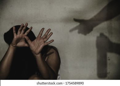 Woman victim of domestic violence and abuse. Woman scared of a man holding alcohol bottle.