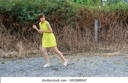 Woman victim in yellow dress run away from thief, man with stipe shirt and black mask, holding sharp knife. How to survive, self-protection, criminal, kidnap, property & life Insurance concept