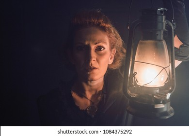 Woman with Victorian outfit holding a gas lamp and looking at the camera with scared reaction.