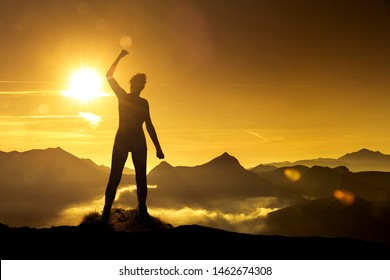 Woman in victory pose at sunrise on a mountain peak Silhouette