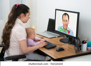 Woman Video Conferencing With Male Friend On Computer At Home