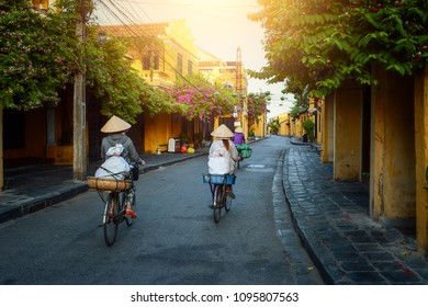 Woman Vietnam riding bicycle  on during sunrise,Hoian Vietnam