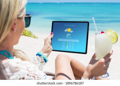 Woman viewing weather forecast on tablet while relaxing on the beach - Shutterstock ID 1896786187