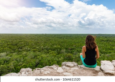 Woman views over the rain forest of Yucatan, Mexico, from the top of the Nohoch Mul pyramid in Coba