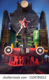 A woman in a vintage black dress posing on an old locomotive. Portrait of a fashionable woman in retro style.