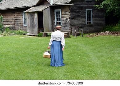 Woman in vintage clothing walking toward log cabin