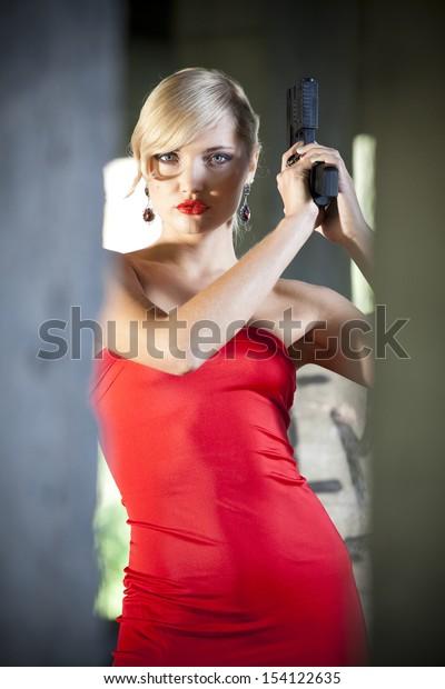 Woman in vintage look holding handgun in old fabric ruins