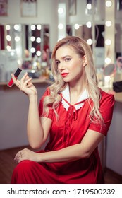 Woman in a vintage red dress in the dressing room sits on a chair and holds her lipstick like a cigarette