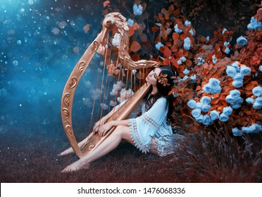 Woman in a vintage short dress with bare legs. A goddess with a gold laurel wreath sits in the garden near blooming roses and hydrangeas with a harp. Light and blessing pours on the girl from heaven
