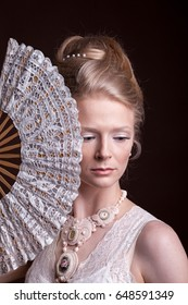 Woman in vintage victorian dress with a oriental fan in hand. Rich and vintage. Luxury and elegance. Studio photo