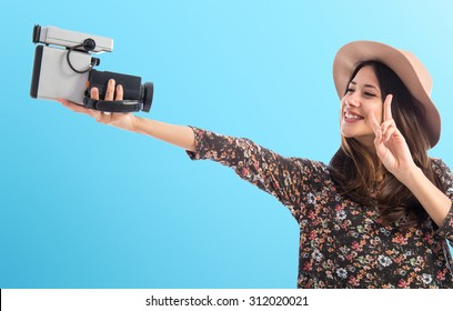 Woman with vintage video camera over colorful background