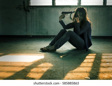 Woman in violence with gun in hand sitting in abandoned building, kill oneself concept. Film gain effect.