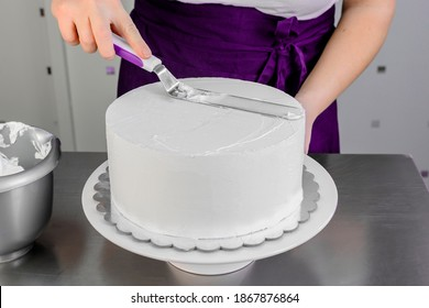 Woman in violet apron using spatula for whipped cream on cake.