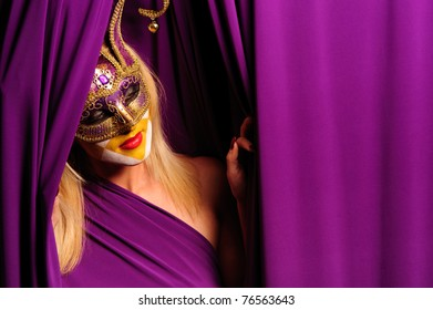 Woman in violet mask posing near curtain