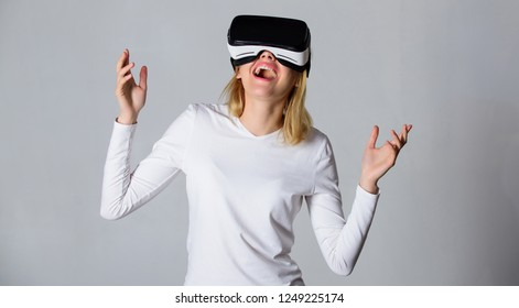 Woman with virtual reality headset. Portrait of an amazed girl using a virtual reality headset isolated on grey background. Funny young woman with VR. Woman VR