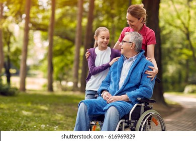 woman visiting her disabled father in wheelchair with granddaughter and enjoying time together in the park
