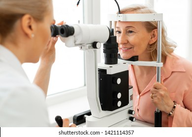 Woman visiting ophthalmologist. Pleasant short-haired woman with blue eyes having her eyes checked in binocular apparatus