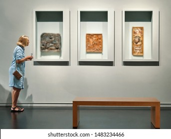 woman visitor looking pictures in art gallery museum
