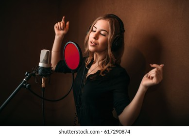 Woman vocalist in headphones against microphone